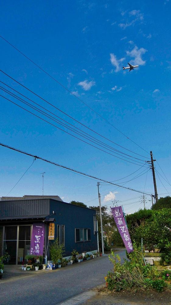 佐藤豆腐店の上空を飛ぶ飛行機