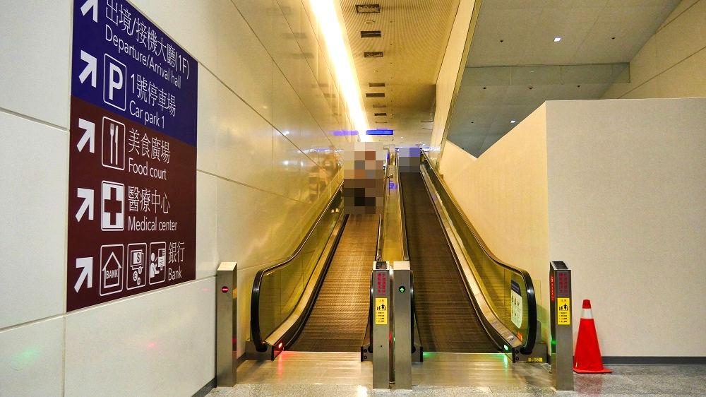 桃園捷運(MRT空港線)へ通じる階に降りるエスカレーター